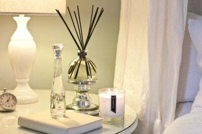 beautiful Pairfum products in the bedroom: perfume spray, luxury scented candle, fragranced reed diffuser, natural / organic / healthy / oil serum / hand-made in the UK