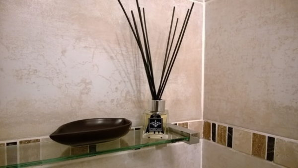 PAIRFUM luxury and natural reed diffuser on a shelf of a modern bathroom