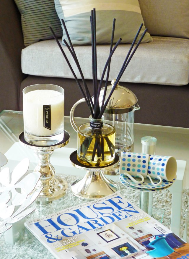 PAIRFUM luxury scented candle and natural reed diffuser on a coffee table