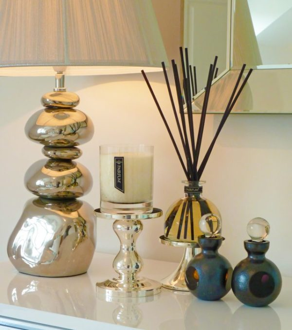 PAIRFUM luxury scented candle and natural reed diffuser on a side table