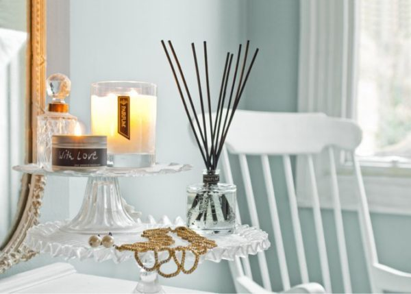 PAIRFUM luxury scented candle and natural reed diffuser on a side table in a French cottage